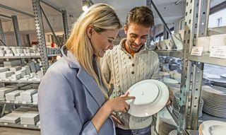 Ein Parchen Schaut Sich Beim Werksverkauf In Einer Porzellanmanufatur Einen Teller Aus Porzellan Genauer An